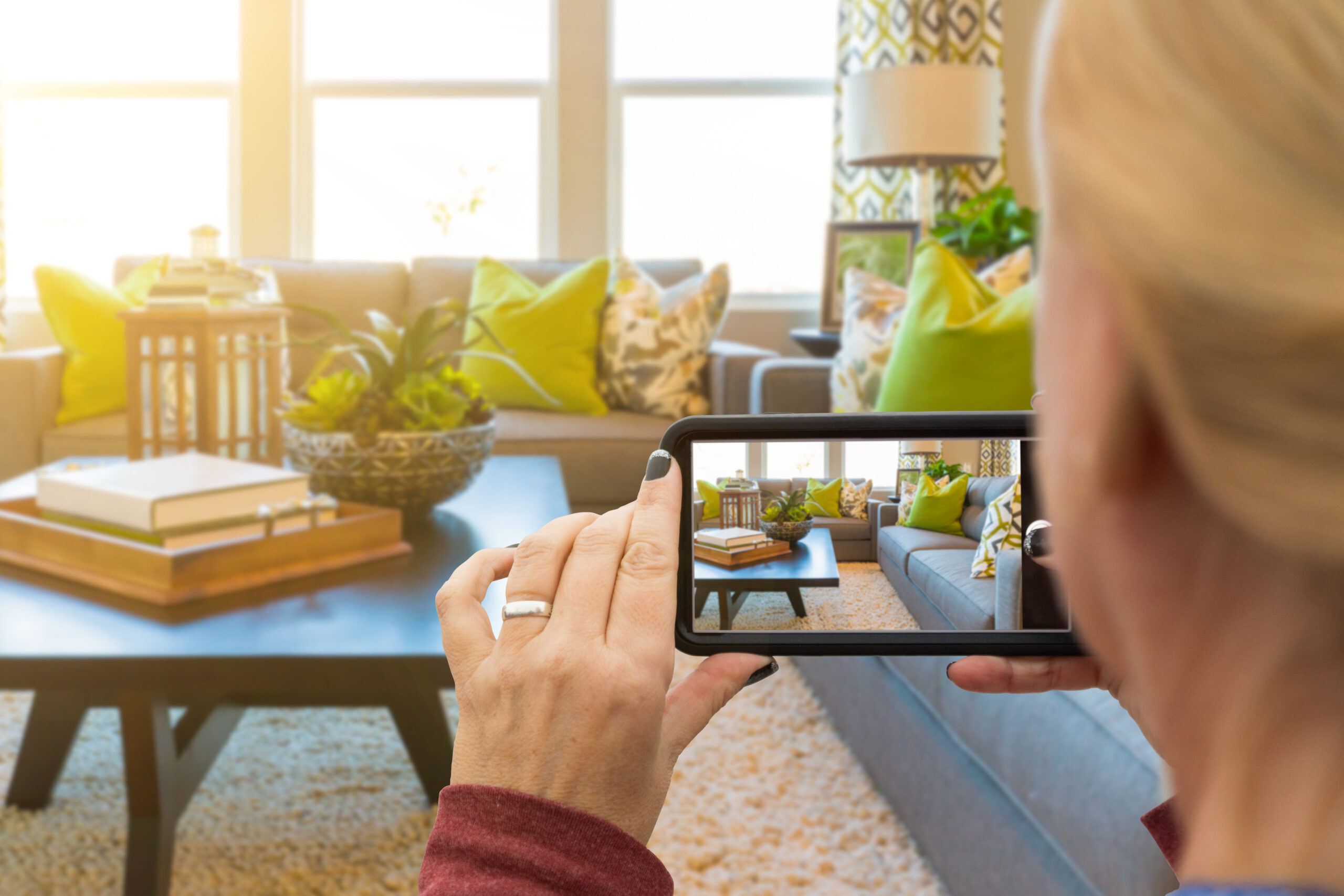 Woman Taking Pictures of A Living Room in Model Home with Her Smart Phone